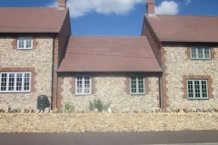 Medium Faced Flint Stone House with Large Faced Flint Stone Wall